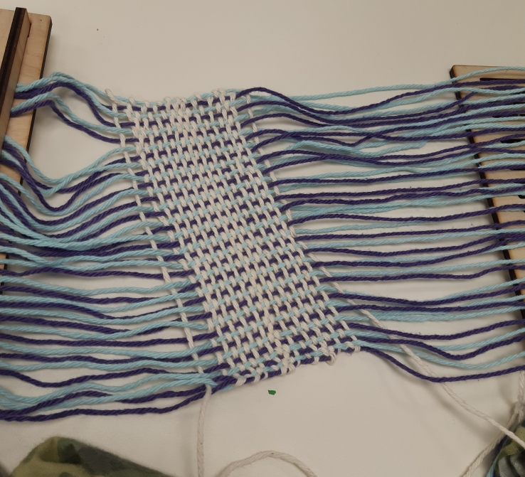 Picture of laser-cut rigid heddle backstrap loom used in a Fine Arts fiber-arts class, for demonstration and practice, and to stimulate conversation around innovation; Photo by Maria Kilfoil