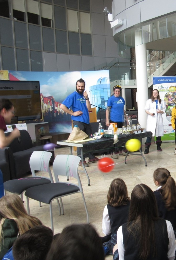 Let's Talk Science volunteers Alberto Nuñez Teijero, Ally Groenen, and Heather Spicer demonstrating activities with the help of children; photo by D. Walsh.